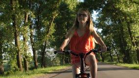 Cute blond teenage girl on bicycle trip in summer