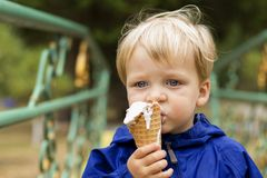 Cute blonde toddler boy in a blue jumpsuit eating Ice Cream stock images