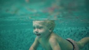 Cute blonde toddler is diving under the water in the swimming pool and swimming there until his mother is lifting him. From the water. An underwater shot stock footage
