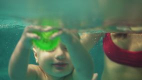 Cute blonde toddler is diving under the water in the swimming pool to get his toy while his mother is teaching him how. To swim. An underwater shot stock footage