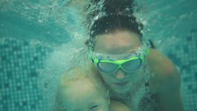 Cute blonde toddler is diving under the water together with his mother in special protective glasses in the swimming. Pool. His mother is teaching him how to stock video