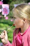 Cute blonde toddler girl eating lollipop. Sitting in the park on a sunny summer day Royalty Free Stock Image