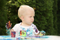 Cute blonde toddler smeared with a gouache. Little painter. Cute artist Royalty Free Stock Photos