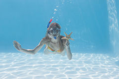 Cute blonde underwater in the swimming pool with snorkel and starfish stock images