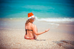 Cute blonde woman in bikini and santa hat sitting on exotic tropical beach. Holiday concept for New Years Cards. Stock Images