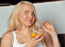 Cute blonde woman eating fruit Stock Images