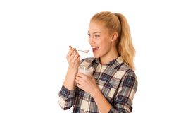 Cute blonde woman eating fruit yogurt isolated over white backgr Stock Images