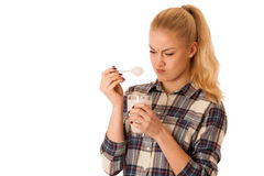Cute blonde woman eating fruit yogurt isolated over white backgr Stock Photo