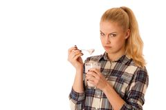 Cute blonde woman eating fruit yogurt isolated over white backgr. Ound Royalty Free Stock Images