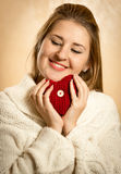 Cute blonde woman embracing red knitted heart Royalty Free Stock Images