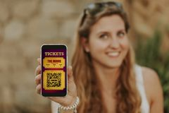 Cute blonde woman holding a mobile phone in the hand with cinema tickets in the screen. Electronic cinema tickets in a mobile phone screen Stock Photos
