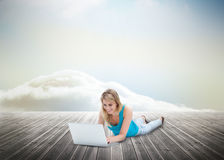 Cute blonde woman laying and using laptop over wooden boards Stock Photo