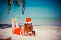 Cute blonde woman in red dress and santa hat lying on exotic tropical beach at palm tree uses mobile phone. Holiday Stock Photos