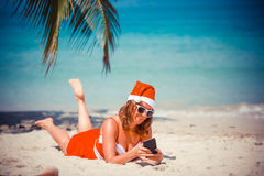 Cute blonde woman in red dress, sunglasses and santa hat lying on exotic tropical beach at palm tree uses mobile phone Stock Photo