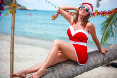 Cute blonde woman in red dress, sunglasses and santa hat sitting on palm tree at exotic tropical beach. Holiday concept Stock Photo
