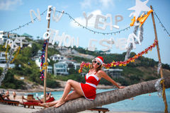 Cute blonde woman in red dress, sunglasses and santa hat sitting on palm tree at exotic tropical beach. Holiday concept Stock Image