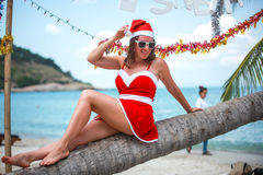 Cute blonde woman in red dress, sunglasses and santa hat sitting on palm tree at exotic tropical beach. Holiday concept Royalty Free Stock Images
