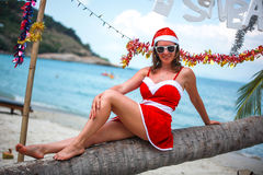 Cute blonde woman in red dress, sunglasses and santa hat sitting on palm tree at exotic tropical beach. Holiday concept Royalty Free Stock Image