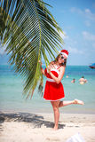 Cute blonde woman in red dress, sunglasses and santa hat stands at palm tree on exotic tropical beach. Holiday concept Stock Photography