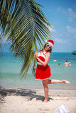 Cute blonde woman in red dress, sunglasses and santa hat stands at palm tree on exotic tropical beach. Holiday concept Royalty Free Stock Image