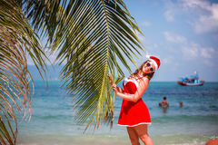 Cute blonde woman in red dress, sunglasses and santa hat stands at palm tree on exotic tropical beach. Holiday concept Royalty Free Stock Photos
