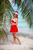Cute blonde woman in red dress, sunglasses and santa hat stands at palm tree on exotic tropical beach. Holiday concept Royalty Free Stock Photography