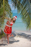 Cute blonde woman in red dress, sunglasses and santa hat stands at palm tree on exotic tropical beach. Holiday concept Stock Photo