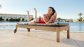 Cute blonde woman in red swimsuit browsing internet on smart phone while lying on deck chair near pool side area. Relaxed girl texting message and blogging stock footage