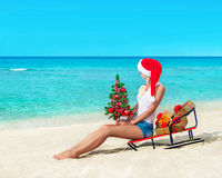Cute blonde woman at sea beach in santa hat sitting at sled with Royalty Free Stock Image