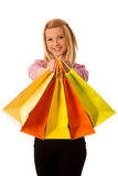 Cute blonde woman with shopping vibrant bags isolated over white Royalty Free Stock Images