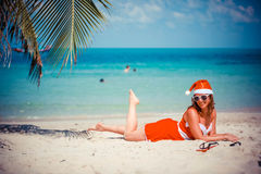 Cute blonde woman in sunglasses, red dress and santa hat lying on exotic tropical beach at palm tree. Holiday concept Royalty Free Stock Image