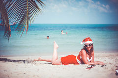 Cute blonde woman in sunglasses, red dress and santa hat lying on exotic tropical beach at palm tree. Holiday concept Stock Photography