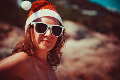 Cute blonde woman in sunglasses and santa hat on at exotic tropical beach in retro colors. Holiday concept for New Years Stock Photography