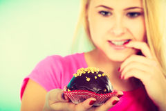 Cute blonde woman thinking about eating cupcake. Diet, sweets, food concept. Cute blonde attractive woman thinking about eating delicious chocolate cupcake stock image