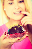 Cute blonde woman thinking about eating cupcake. Diet, sweets, food concept. Cute blonde attractive woman thinking about eating delicious chocolate cupcake stock photos
