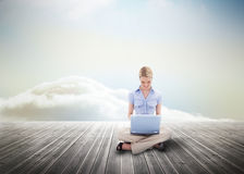 Cute blonde woman using laptop over wooden boards Royalty Free Stock Photo