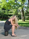 Cute blonde woman waits by road Stock Images