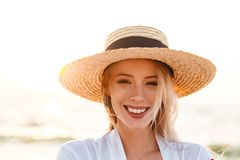 Cute blonde woman wearing hat outdoors at the beach. Image of beautiful cute blonde woman wearing hat outdoors at the beach looking camera Royalty Free Stock Image