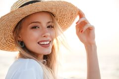 Cute blonde woman wearing hat outdoors at the beach. Image of beautiful cute blonde woman wearing hat outdoors at the beach looking camera Royalty Free Stock Images