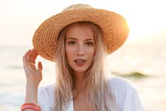 Cute blonde woman wearing hat outdoors at the beach. Image of beautiful cute blonde woman wearing hat outdoors at the beach looking camera Royalty Free Stock Photo