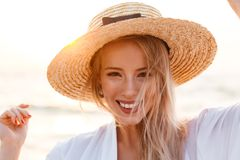 Cute blonde woman wearing hat outdoors at the beach looking camera. Stock Photography