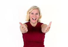 Cute blonde woman in a welcome pose. A blonde woman smiles with arms outstretched in a welcome, inviting expression Stock Photo
