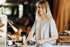 A cute blonde youg girl,wearing casual outfit,stands next to the coffee machine and smile in a cozy coffee shop. royalty free stock photography
