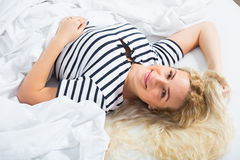 Cute blondie lounging in bed at home Royalty Free Stock Photos