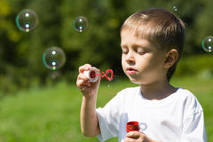 Cute blowing soap bubbles in a park Stock Images