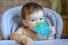Cute blue-eyed baby boy holding plastic mug in his hands and drinking water itself lookin at camera, royalty free stock photos