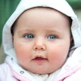 Cute blue-eyed baby. Portrait of a cute blue-eyed baby girl close up royalty free stock images