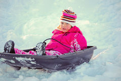 Cute blue eyed girl on a sled in the snow. Royalty Free Stock Photo