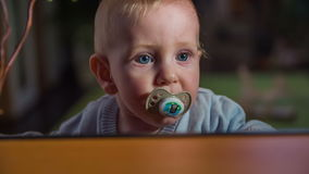 Cute blue eyes baby putting the pacifier in his mouth. Close up slow motion footage of a beautiful blue eyes baby boy putting the pacifier in his mouth behind stock video footage