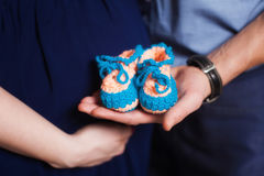 Cute blue knitted baby booties on hands. Pregnancy concept Stock Photos